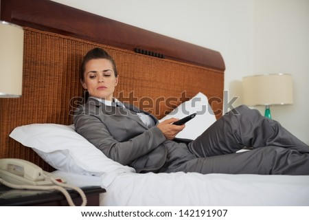 Concerned business woman laying on bed in hotel room and waiting phone call