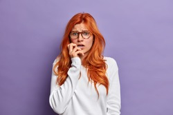 Concerned embarrassed redhead woman looks with panic at camera, stares insecure and bites finger nails nervously. Scared trembling lady has dissatisfied expression, poses against purple background