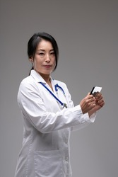 Concerned female Asian doctor or nurse standing holding a mobile phone in her hands as she turns to look at the camera over a grey studio background with copyspace