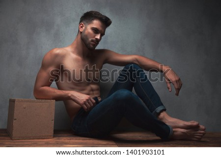 Concerned man resting his arm on his knee, frowning and looking to the side while leaning on a box and sitting on gray studio background