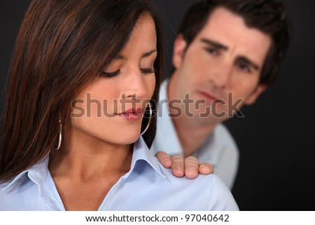 Concerned man touching his wife's shoulder - stock photo