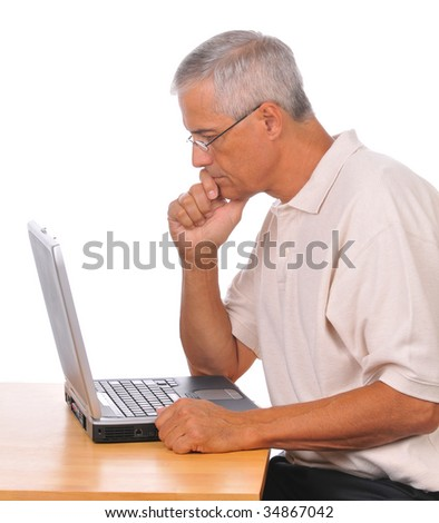 Concerned Middle Aged  Businessman Seated at Computer seen from the side isolated on white