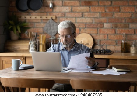 Concerned older aged male check documents invoices from home office using computer deal with debt mistake in papers. Thoughtful serious senior man provide loan mortgage utilities payment online on pc Photo stock ©