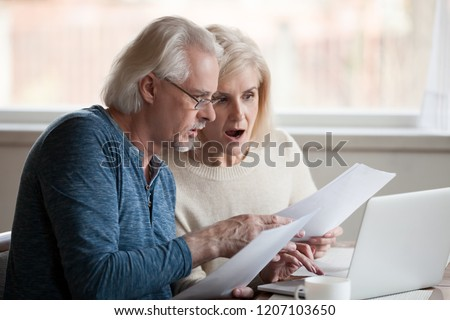 Concerned senior husband and wife hold documents using laptop checking information online, worried aged couple shocked by prices or tax growth reading bills on computer, man and woman have pc problem Stock photo ©