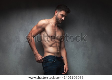 Concerned shirtless guy looking to the side and pulling up his jeans while leaning against gray studio background