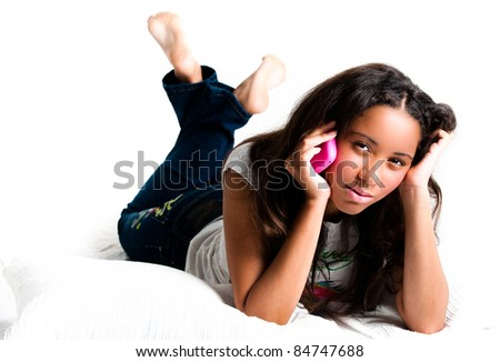 Concerned teenage girl on a pink cell phone lying down listening with legs crossed feet in the air - isolated on white