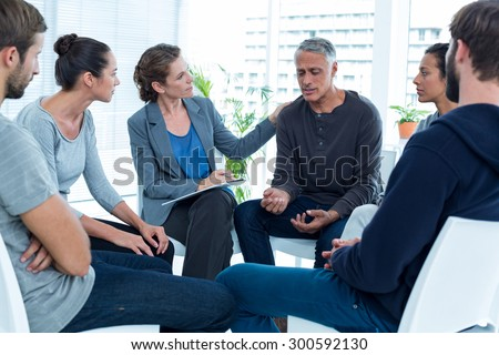 Concerned woman comforting another in rehab group at a therapy session