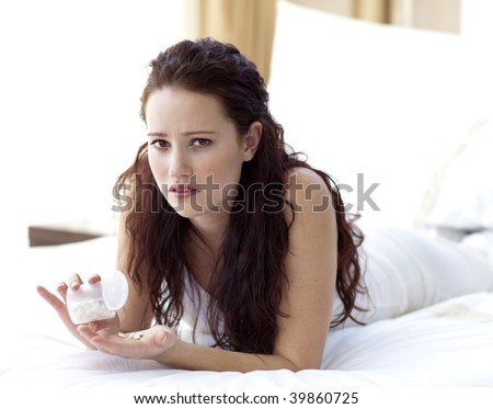 Concerned woman lying in bed taking pills