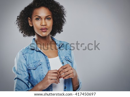 Concerned woman with blue jean shirt holds hands together in front of her on gray background
