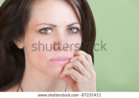 Concerned young Caucasian woman on green background with fingers to chin