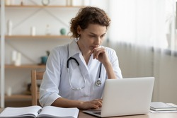 Concerned young female Caucasian doctor in white medical uniform sit at desk in hospital work on laptop, focused woman nurse or GP busy fill anamnesis on computer gadget, medicine, technology concept