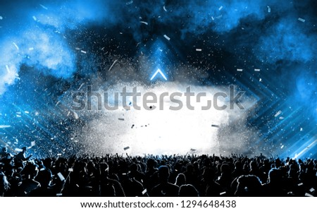 Concert background with the many people standout look at stage with smoke effect and light is really happy time.