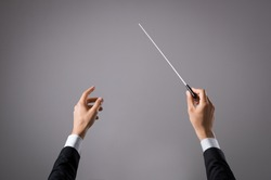 Concert conductor hand with baton isolated on grey background. Chorus composer holding baton during a opera. Musician directing concert. Close up hands of orchestra conductor with copy space.