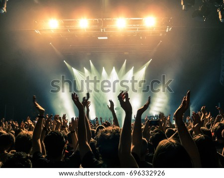 Photo of  Concert crowd attending a concert, people silhouettes are visible, backlit by stage lights. Raised hands and smart phones are visible here and there.
