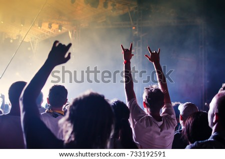 Concert Crowd. Silhouettes young people in front of bright stage lights. Band of rock stars #733192591