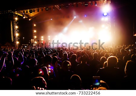 Concert Crowd. Silhouettes young people in front of bright stage lights. Band of rock stars #733222456