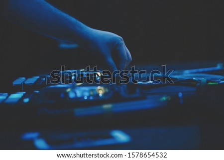 Concert dj playing music on techno party in music hall.Professional disc jockey mixes musical tracks on edm festival using digital turntable deck and sound mixer on scene in blue lights