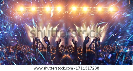 Concert festival during the main event, a big crowd is visible in front of the stage, lit up for the gig. People is unrecognizable, lens flare is present. Foto stock ©