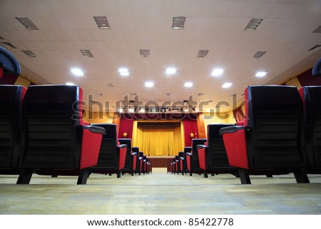 Concert hall and empty stage, many rows of red seats and stage with yellow curtain; view from floor