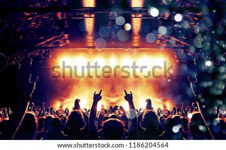 Concert hall with colourful lights and clapping hands #1186204564