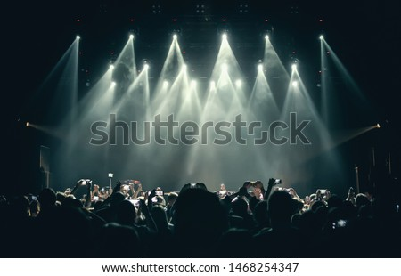 Photo of Concert stage lights & crowd on dance floor partying to the music.Group of young people with smartphones having fun on dancefloor in nigth club.Bright stage lights and silhouettes of fans with phones