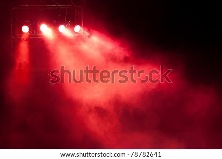 concert stage with red spot light and smoke