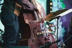 Concert view of a contrabass violoncello player with vocalist and musical band during jazz orchestra band performing music, violoncellist cello jazz player on stage