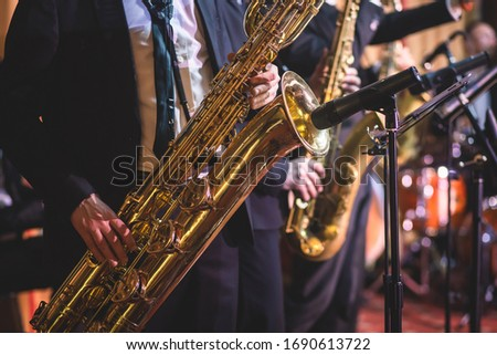 Concert view of a saxophonist, saxophone player with vocalist and musical during jazz orchestra performing music on stage  Сток-фото ©
