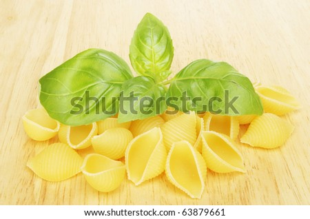 Conchiglie pasta and fresh basil herb leaves on a wooden board