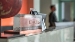 Concierge service counter of hotel, restaurant or apartment's front desk in luxury reception hall with staff working for serving tourist guest or check-in customers