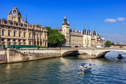 Conciergerie Castle and Seine River with cruise tour boat. Castle Conciergerie is a former prison, located on west of the Cite Island and today it is a part of Palais de Justice. Paris, France
