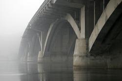 Concrete arch bridge over the river in the fog