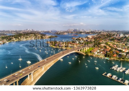 Concrete arch of Gladesville bridge over Parramatta river in Sydney Inner West with view of distant Sydney city CBD and local marina docked floating yachts.