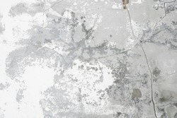Concrete background. White flaky plaster over unpainted concrete wall