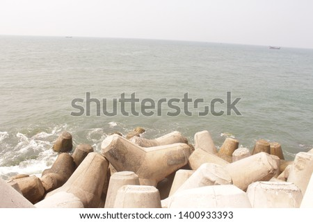 Concrete barriers in the shore, sailing boats in distance and it looks a calm sea for activities to go on and to take place.