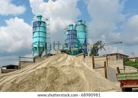 Concrete batching plant with three silos, heap of sand and gravel