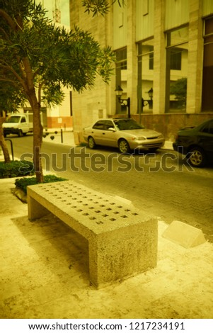 Concrete bench of Santo Domingo street. Bench is lit with soft sun light falling through the clouds in warm autumn day. Bench stands on sidewalk. Some old cars are parked near. Vintage style photo
