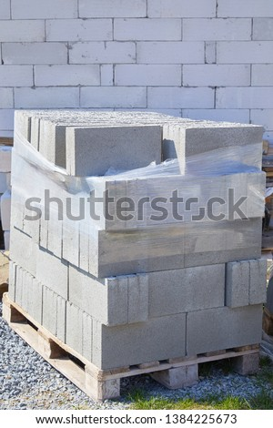 Concrete block bricks in stack for wall construction. Concrete block, cinder blocks, breeze blocks, hollow blocks, Besser blocks or Besser bricks wall background, brick texture #1384225673