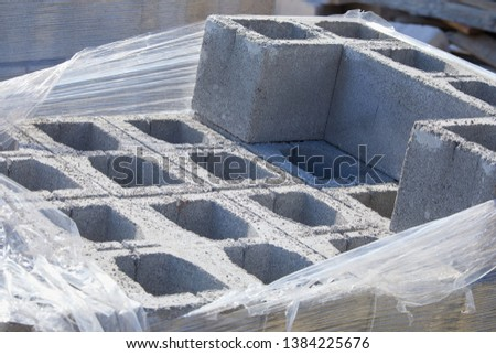 Concrete block bricks in stack for wall construction. Concrete block, cinder blocks, breeze blocks, hollow blocks, Besser blocks or Besser bricks wall background, brick texture #1384225676