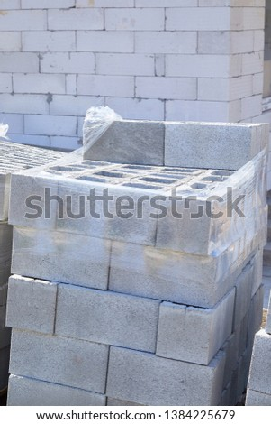 Concrete block bricks in stack for wall construction. Concrete block, cinder blocks, breeze blocks, hollow blocks, Besser blocks or Besser bricks wall background, brick texture #1384225679