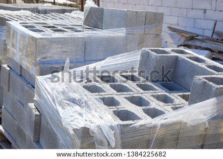 Concrete block bricks in stack for wall construction. Concrete block, cinder blocks, breeze blocks, hollow blocks, Besser blocks or Besser bricks wall background, brick texture #1384225682