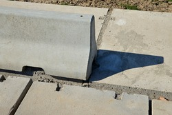 Concrete block separating the panel road from the pavement. road made of panels with concrete divider. Jersey barrier, Jersey wall, modular concrete barrier employed to separate lanes of traffic.