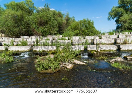 Concrete blocks lying on a small river - dam #775851637