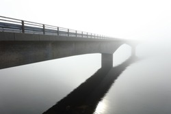 Concrete bridge over the sea in the middle of a deep fog