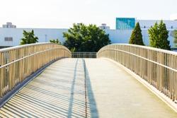 Concrete bridge with metal railing. Curved foot bridge. Street photo.
