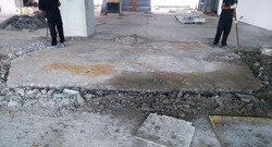 Concrete chipping work at  site.wastage in construction.Removing of excess unwanted concrete from floor.