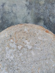 Concrete circle propped against an unpainted cement wall.