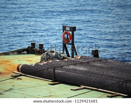 Concrete coated line pipes are secured on material barge at offshore with blue sea background.