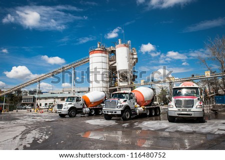 Concrete company and three mixer trucks in a blue sky day.