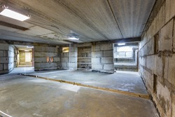 Concrete construction of basement of large building. Ground floor Inside the modern construction site in a mix of fluorescent and natural lights. Contemporary structure under construction with concret